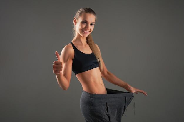完璧な健康的な薄い体を持つ若い女性のスリムウエスト