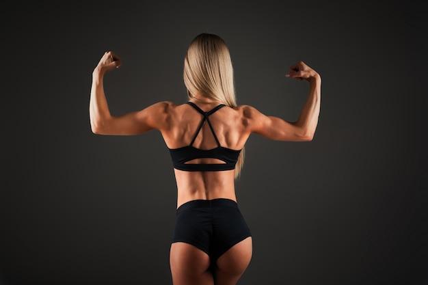 強い運動女性フィットネスモデル、背中の筋肉をポーズ