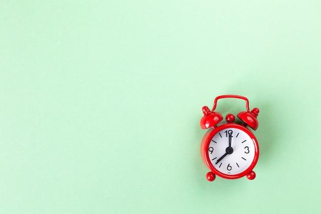明るいパステルグリーンの背景に赤の小さな目覚まし時計