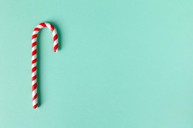パステルターコイズブルーの背景にクリスマスペパーミントキャンデー杖。