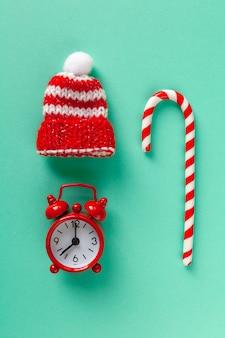 パステルターコイズブルーの背景にクリスマスキャンデー杖、時計、帽子。