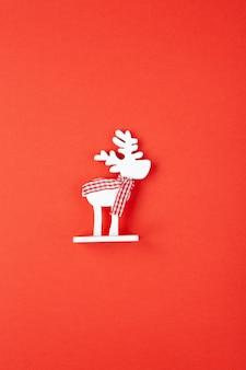 Новогоднее украшение, игрушка белый олень в клетчатом шарфе на красном фоне