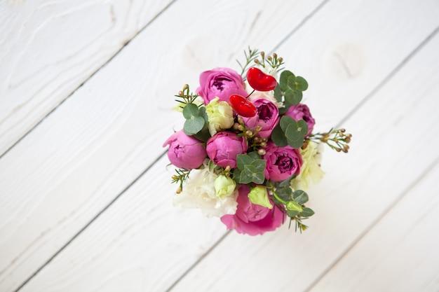 白い木製の表面に創造的な花の花束
