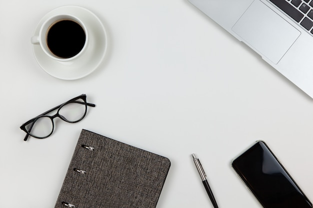モダンなユニセックスの作業スペース、トップビュー。メモ帳、ペン、コーヒー、スマートフォン、メガネ、白い背景の上のラップトップ、コピースペース、フラットレイアウト