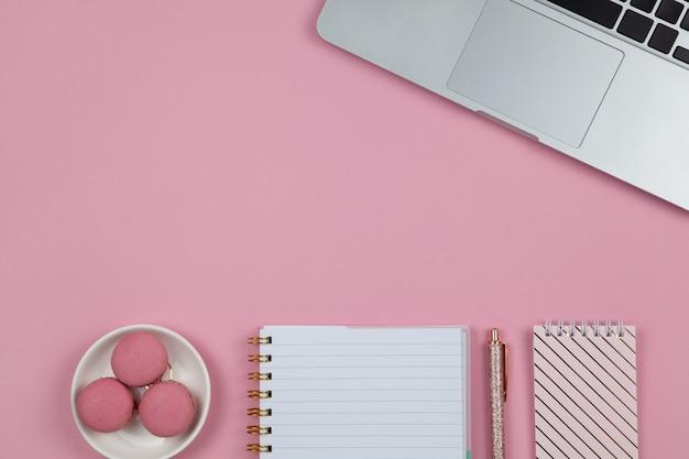 Современное женское рабочее пространство, вид сверху. ноутбук, блокноты, ручка в цвете розового золота, макаруны на розовом фоне, копией пространства, плоская планировка