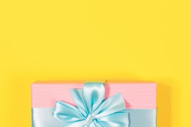 ピンクのギフトボックスは、黄色の背景の上に弓で青いリボンで結ばれています。テキスト用のスペースをコピーします。最小限の平置き。