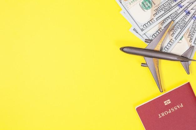 Доллары, самолет, наушники, загранпаспорт на желтом фоне. копировать пространство