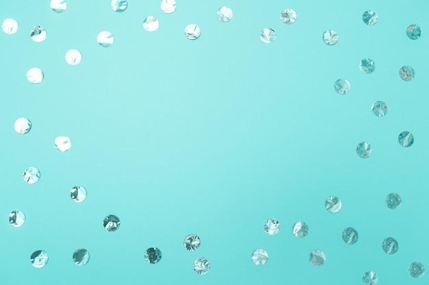 パステル調のターコイズブルーの背景に光沢のある銀の紙吹雪のフレーム