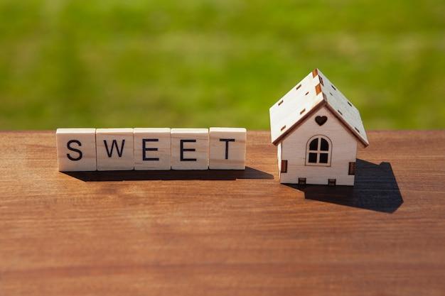 Слово сладкое из деревянных букв и небольшой игрушечный деревянный дом на коричневой поверхности