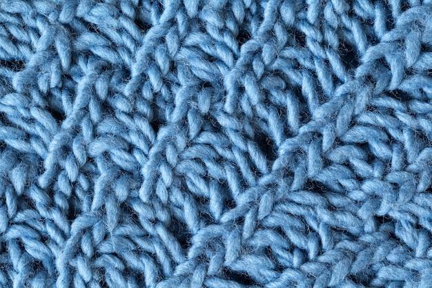 ニットウールの織り目加工の表面、マクロ。柔らかいグレーブルーメリノウールパターン背景、クローズアップ。秋と冬の平干し。スカンジナビアのミニマルスタイル