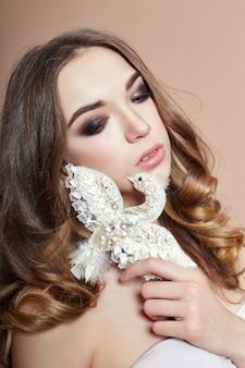 若者のファッションのブロンドの女の子とブローチの鳥の宝石類