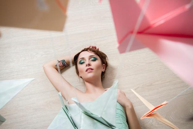 Девушка мечтает на фоне бумаги птиц. оригами