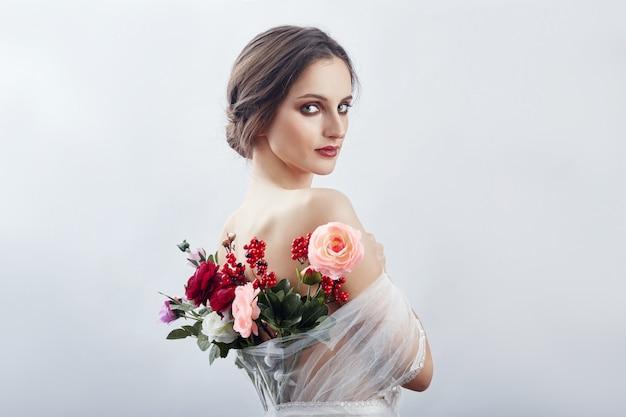 背後にある造花の花束を持つ女性