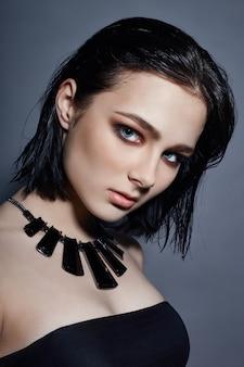 彼女の首の周りのセクシーなファッションの女の子黒髪宝石
