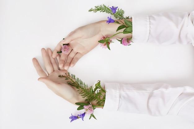 手と春の色の花はテーブルのスキンケアにあります