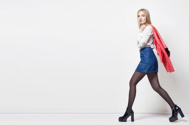 Красивая сексуальная белокурая женщина в рубашке и юбке