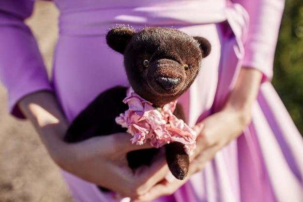 手にテディベアを持ってピンクのドレスの女の子