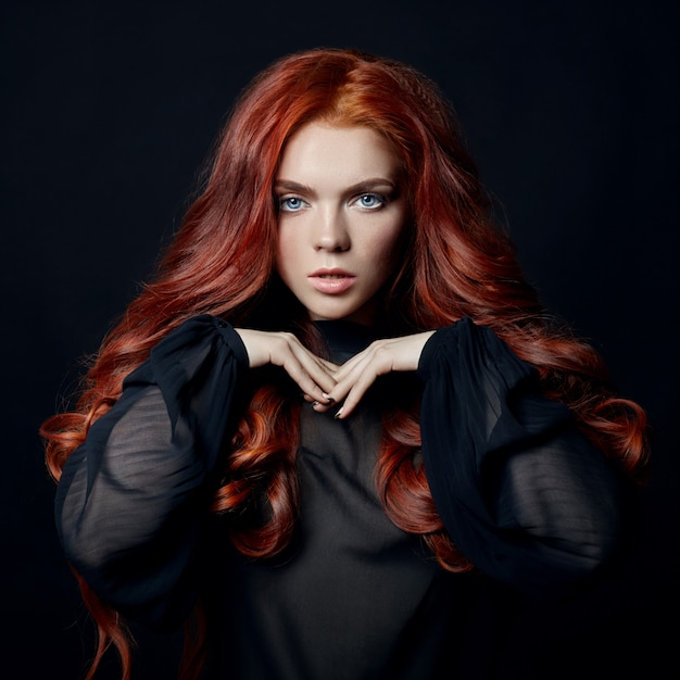 黒の背景に赤い髪を持つ美しい女性