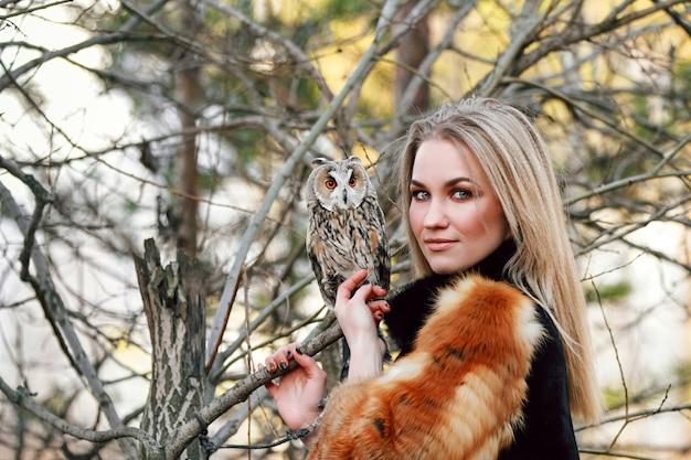 一方でフクロウと毛皮のコートで美しい女性
