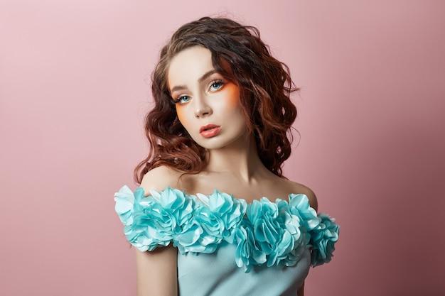 ターコイズブルーのドレスでセクシーな女性の美しい化粧