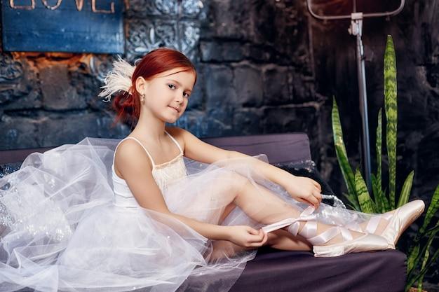 白いボールガウンと靴、美しい赤い髪の少女。若い演劇女優。小さなプリマバレエ。若いバレリーナ少女はバレエ公演の準備をしています