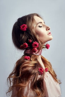 彼女の長い髪にバラの花を持つ美しい女性