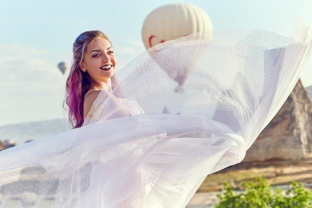 Девушка стоит на холме и смотрит на большие воздушные шары