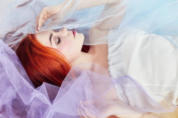 明るい色のドレスで赤毛の女の子が床にあります。