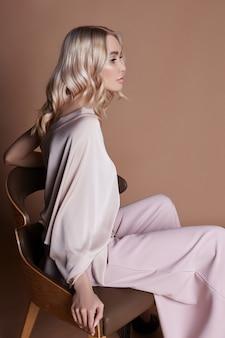 椅子に座っているドレスでセクシーな豪華な女性。秋のコレクション