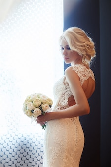 朝の花嫁。花の花束を保持している白いウェディングドレスの女性