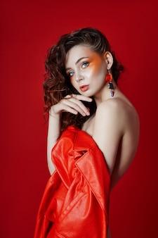 Красивый макияж сексуальной обнаженной женщины в красной куртке на красном