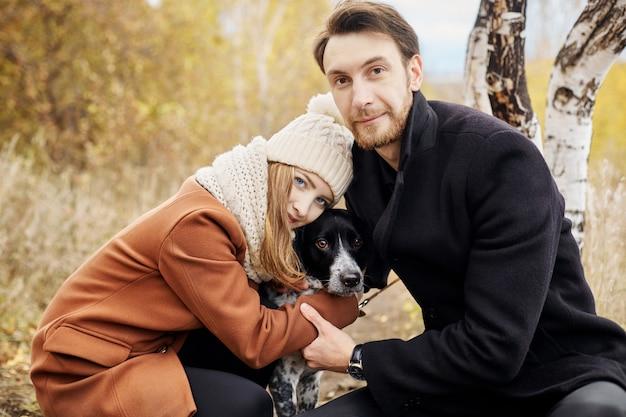 公園で犬と散歩とハグのカップル
