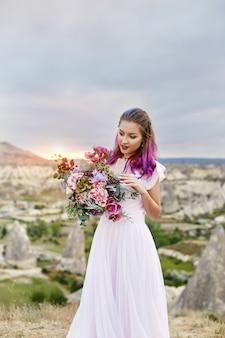 彼女の手に花の美しい花束を持つ女性が立っています。