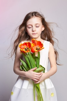 Мода рыжеволосая девушка с тюльпанами в руках. студийное фото