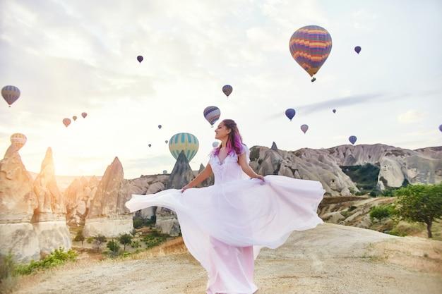 カッパドキアの風船の上の長いドレスを着た女性