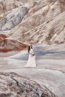 明るい夏のドレスベージュで美しい少女が山の中を歩く