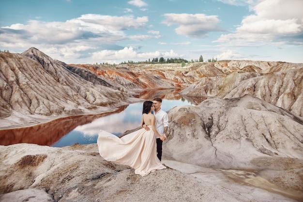 Пара стоит на обрыве горы и красного озера и обнимает