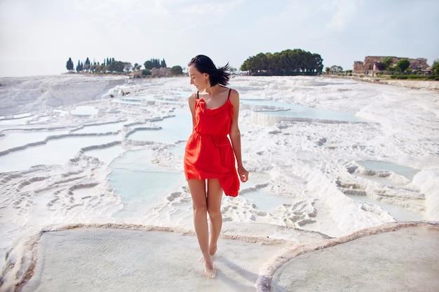 白い山に対して赤いドレスを着た美しい女性が立っています。