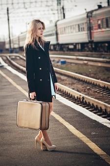 駅で電車を待っているスーツケースと美しいブロンドの女の子