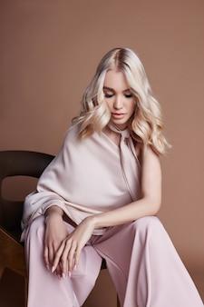 椅子に座っているドレスでセクシーな豪華な女性。女性服の秋コレクション