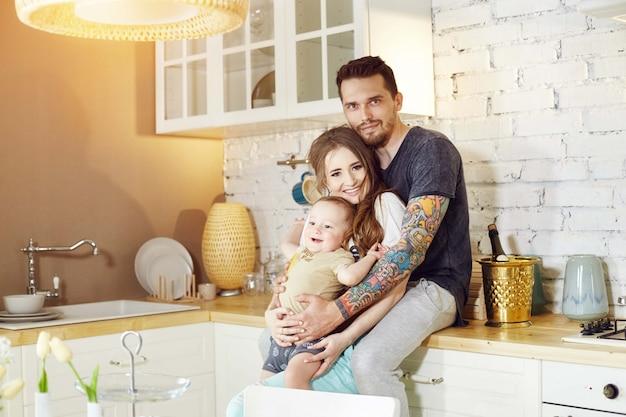 Пара и их маленький ребенок ребенок в руках. молодая семья дома