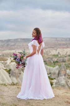 手に花の美しい花束を持つ女性は、夜明けの夕日の光線で山の上に立つ
