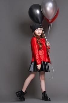 色の風船のファッションの女の子はウインクします。暗い背景のスタジオ写真
