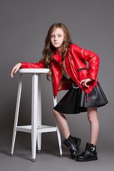 Модная детская девочка в красной кожаной куртке и черной юбке позирует возле табуретки