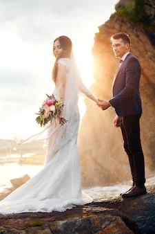 Красивая влюбленная пара целуется на скалах у моря