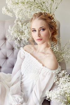 女の子の白い光のドレスと巻き毛、自宅の花を持つ女性の肖像画