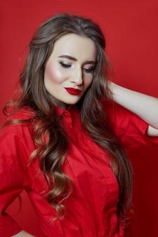 赤い背景の赤い巻き毛のドレスを持つ女性