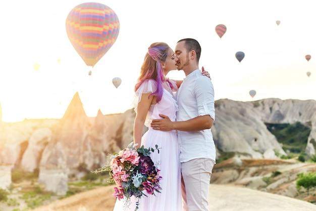 愛のカップルは、カッパドキアの風船の背景に立っています。