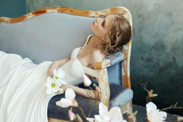 ソファーソファに横たわっているシックなロングドレスの花嫁。白いウェディングドレス