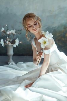 床に座ってシックなロングドレスの女の子。白いウェディングドレス